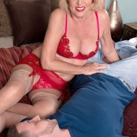 Lingerie, stocking and garter attired mature pornstar giving large cock a handjob