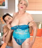 Mature lady in lingerie and tan stockings exposing her large boobs for younger man