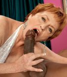 Crimson hair granny XXX actress Valerie fellating a gigantic black prick in white lingerie