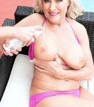 Enticing 60 plus lady Katia has her giant boobs kneaded by younger dude on a patio