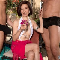 Busty over 60 Asian pornstar Kim Anh blowing two big cocks outdoors by pool