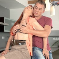 Redhead pornstar over 60 freeing big tits before jerking cock in kitchen