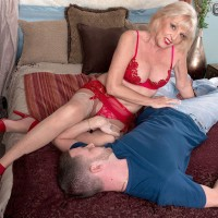 Lingerie, stocking and garter attired mature pornstar giving large cock a handjob