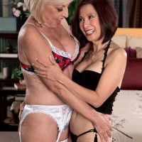 Over 60 mature pornstars Scarlet Andrews and Kim Anh kissing in FFM threesome