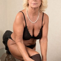 Over 60 babe Regi removing nylons and skirt for nude massage from younger man
