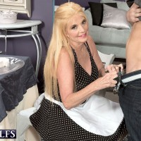60 plus MILF with blonde hair seduces a young man while in a kitchen apron