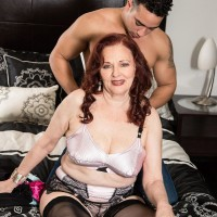 Mature redhead woman has her breasts sucked on by a young boy