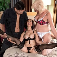 Hot nans tongue kiss during threesome action on a bed in garters and hosiery