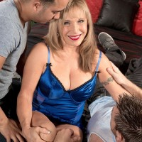 Sexy older woman with blonde hair has her nice tits freed by a couple of boys
