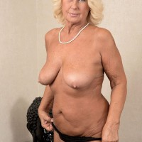 60 plus blonde MILF strips naked before being massaged by a younger gent