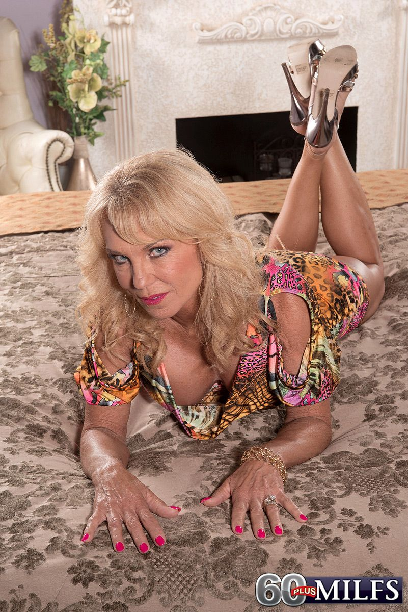 Hot over 60 blonde woman revealing large breasts for nipple licking in high heels