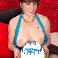 Redhead over 60 lady exposes her large boobs while getting changed by herself