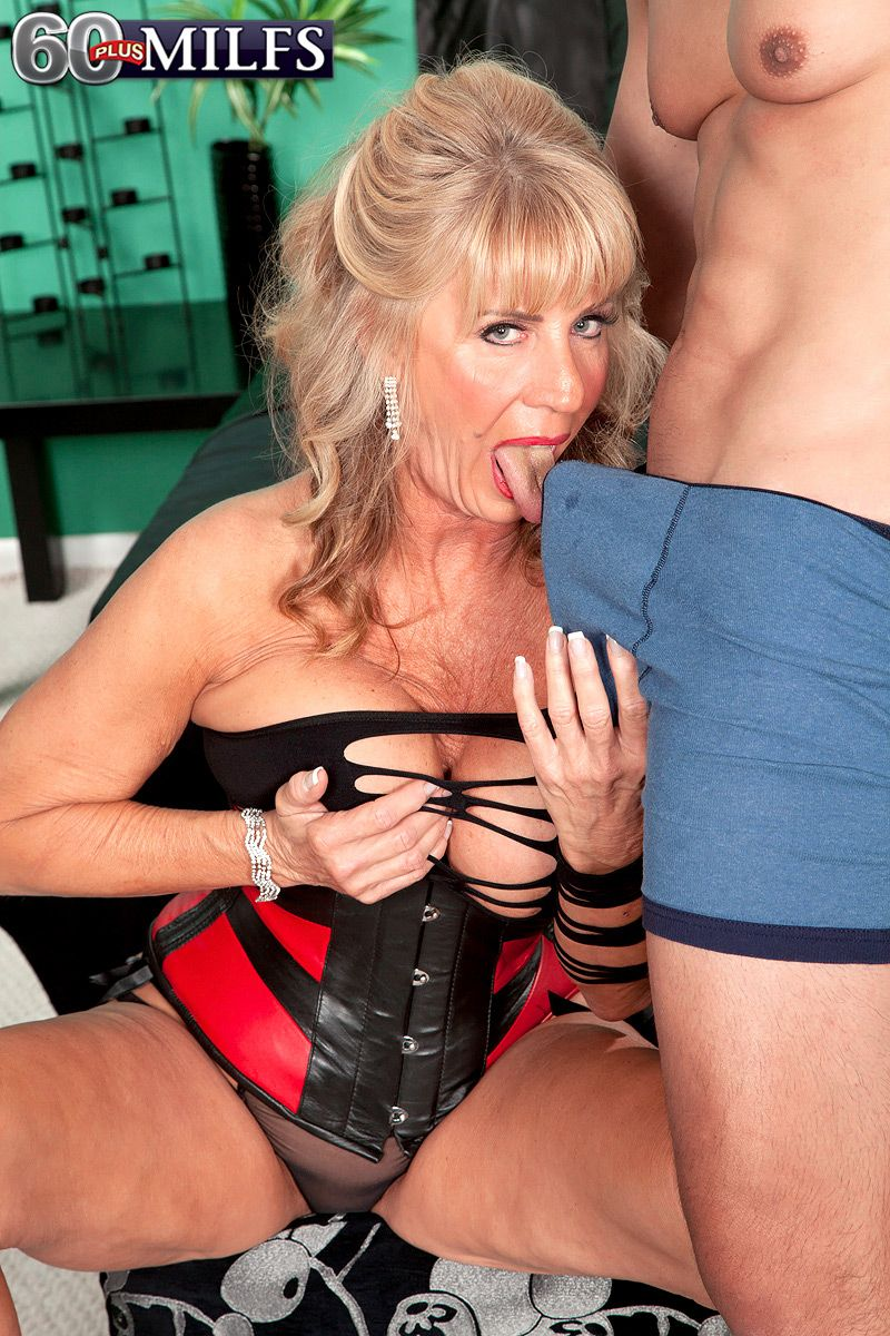 Hot 60 plus woman gets on top of a toy boy wearing a revealing latex dress