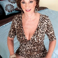60 MILF with short hair strips to a brassiere and pantyhose on her bed