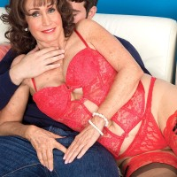 Sexy 60 plus lady has her nipples licked by her boy toy while on a sofa