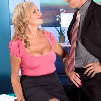 Sexy 60+ blonde seduces a coworker while showing cleavage in a skirt