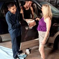 Older blonde woman seduces two younger mechanics inside a garage