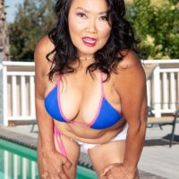 Sixty plus Oriental MILF Mandy Thai strips off a  swimsuit to get bare naked by a pool