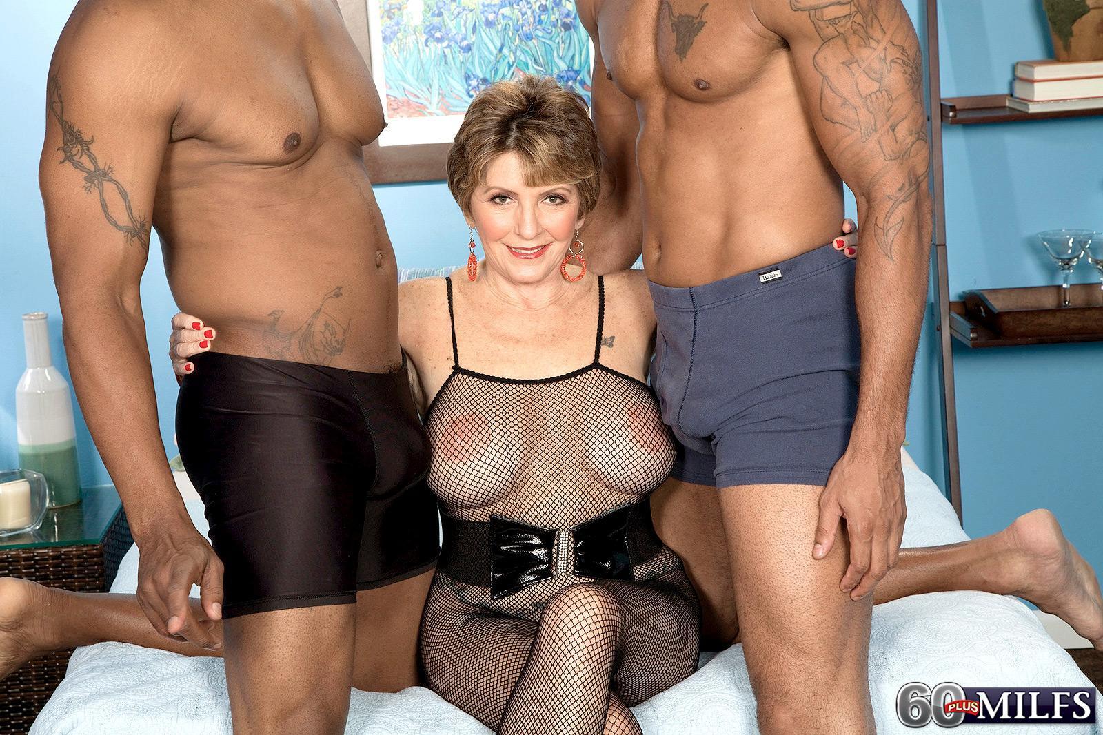 Bosomy sixty plus MILF Bea Cummins jerking big ebony dick in bi-racial threesome sex festival