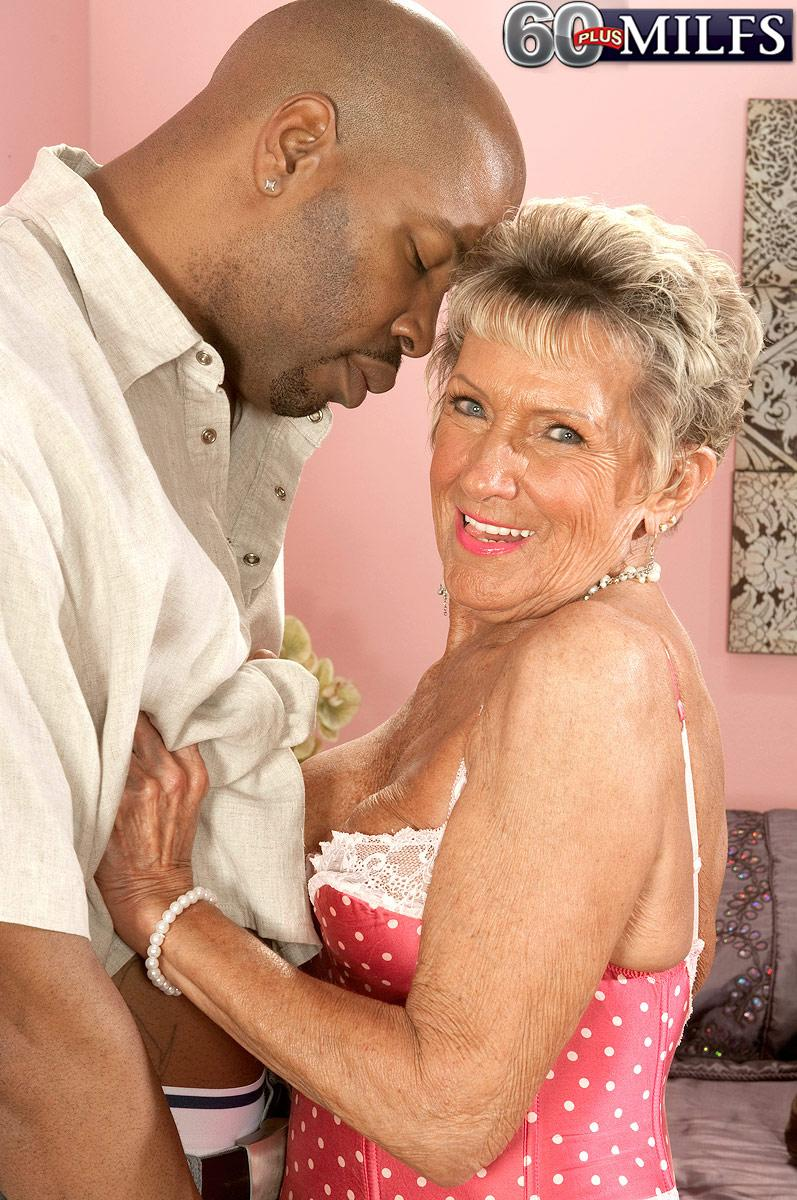 Bosomy stocking and lingerie attired 70 plus grannie Sandra Ann giving huge ebony junk a blow-job
