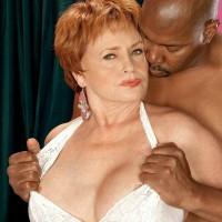 Crimson hair granny XXX actress Valerie fellating a gigantic black prick in white lingerie