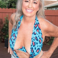 Gorgeous sixty plus MILF Silva Foxx tempts a younger guy by flashing her titties in a denim microskirt