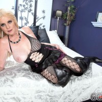 Light-haired granny Charlie bares her gigantic titties in over the knee boots and mesh body-stocking