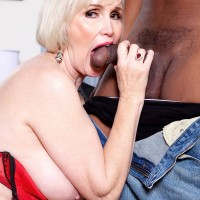 Nylon and lingerie clad grannie Lola Lee delivering huge black penis oral pleasure with enormous breasts out