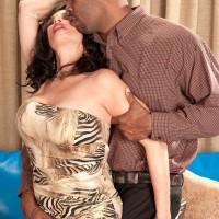Older black-haired pornstar Rita Daniels uncovering hefty funbags before multiracial sex