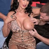 Older dark haired XXX flick star Rita Daniels displaying no panty upskirt during knocker sucking
