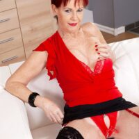 Over 60 redhead Caroline Hamsel plays with her boobies while outfitted in crotchless panties