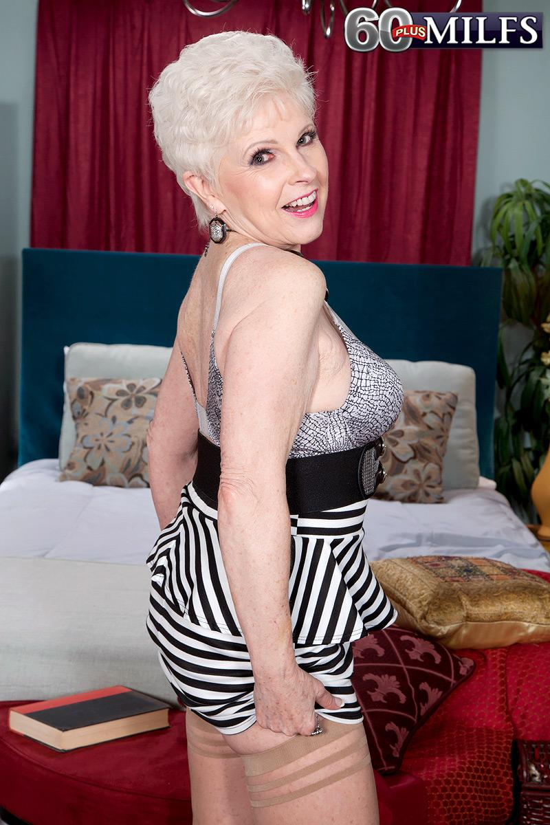 Over sixty MILF pornstar Jewel having immense tits liberated from dress in stockings and high heeled shoes