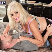 Sandy-haired granny Leah L'Amour gives her dude toy a hand job in lingerie and pantyhose