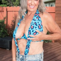 Tempting 60 plus MILF Silva Foxx tempts a younger dude by showing off her fun bags in a denim mini-skirt