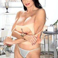 Top experienced adult film starlet Rita Daniels unsheathes her huge breasts and displays her panties too