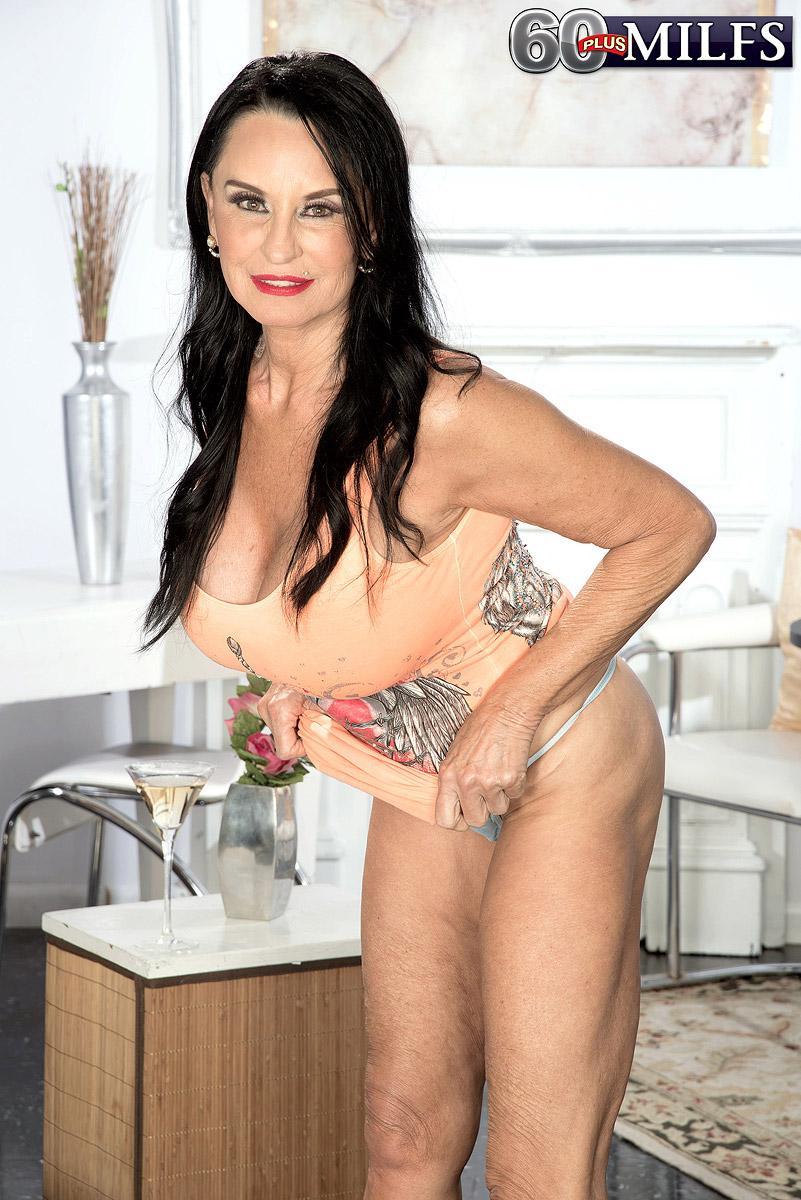 Top experienced adult film starlet Rita Daniels unsheathes her huge breasts and displays her panties too